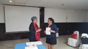 Berta Oliva, coordinadora del Cofadeh le entrega el diploma a Haydeé Saravia de la Coordinadora de Organizaciones Populares del Aguán (COPA)