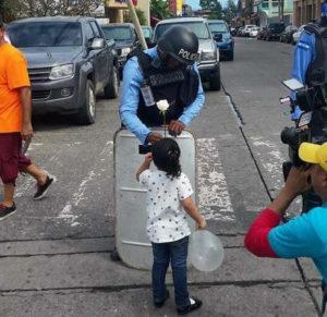 nina da una flor a policia
